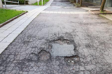 Damaged local street in Gothenburg, Sweden. Road maintenance concept.