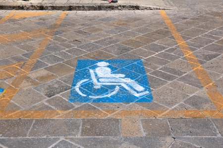 Handicapped parking spot - urban transportation infrastructure road markings in Italy.
