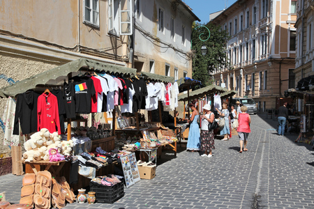 BRASOV, ROMANIA - AUGUST 21, 2012: People visit souvenir stalls in Brasov, Romania. Brasov is a popular tourism destination with 581,983 arrivals in Brasov County in 2008.