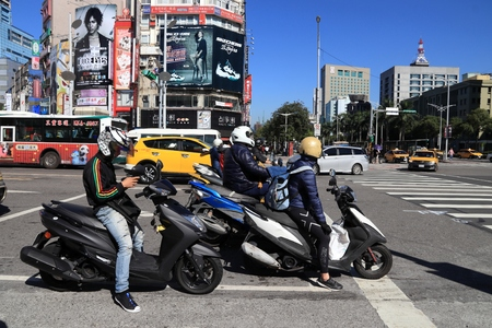 TAIPEI, TAIWAN - DECEMBER 3, 2018: Scooter riders in Ximending shopping district in Taipei. Ximending is considered one of top shopping destinations in Taiwan, catering especially youth shoppers.