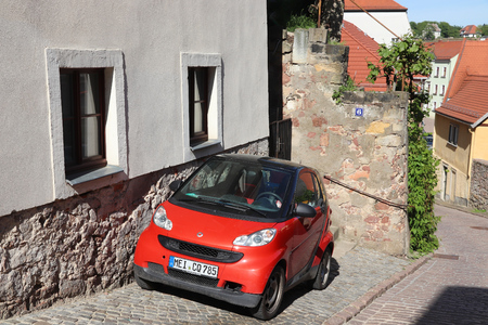 MEISSEN, GERMANY - MAY 5, 2018: Red Smart Fortwo mini city hatchback car parked in Germany. There were 45.8 million cars registered in Germany (as of 2017).