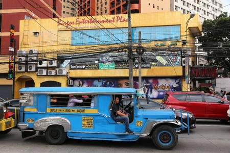 MANILA, PHILIPPINES - DECEMBER 7, 2017: People ride a jeepney public transportation in heavy traffic in Manila, Philippines. Metro Manila is one of the biggest urban areas in the world with 24 million people.