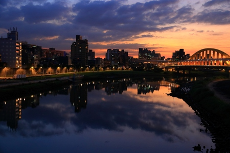 Songshan district sunset cityscape in Taipei. River skyline reflection. Stock Photo