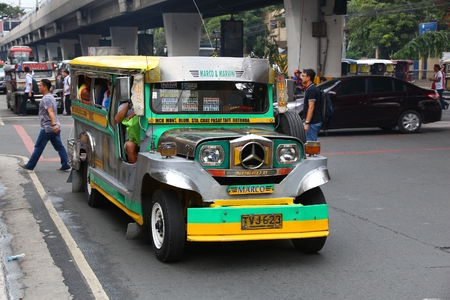 MANILA, PHILIPPINES - NOVEMBER 24, 2017: People ride a jeepney public transportation in heavy traffic in Manila, Philippines. Metro Manila is one of the biggest urban areas in the world with 24 million people.
