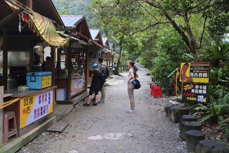 TAROKO NATIONAL PARK, TAIWAN - NOVEMBER 25, 2018: Tourists visit snack huts in Truku tribal village at Taroko National Park, Taiwan.