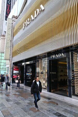 TOKYO, JAPAN - DECEMBER 1, 2016: People walk by Prada luxury fashion store in Ginza district of Tokyo, Japan. Ginza is a legendary shopping area in Chuo Ward of Tokyo.