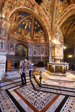 SIENA, ITALY - MAY 3, 2015: People visit the Baptistery in Siena, Italy. The Medieval Baptistry is dedicated to St. John (San Giovanni).