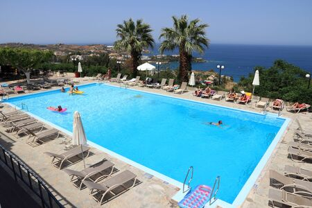AGIA PELAGIA, GREECE - MAY 18, 2013: People relax by a swimming pool in a generic resort in Agia Pelagia, Crete, Greece. Crete attracts 2.8 million annual tourists (2011). Redactioneel
