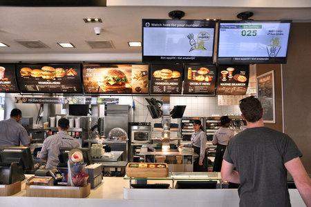 AMSTERDAM, NETHERLANDS - JULY 8, 2017: Employees work the kitchen of McDonald's restaurant in Amsterdam. McDonald's is the world's largest restaurant chain with 69 million customers served daily. Redakční