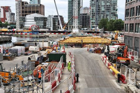LONDON, UK - JULY 8, 2016: Construction workers work on new development in London, UK. Canary Wharf is Londons second financial centre developed in 1991.