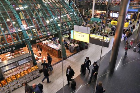 AMSTERDAM, NETHERLANDS - NOVEMBER 21, 2018: Travelers visit Schiphol Airport in Amsterdam. Schiphol is the 12th busiest airport in the world with more than 63 million annual passengers.