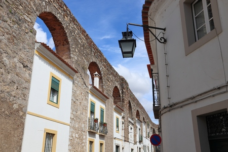 Evora town in Portugal. Prata Aqueduct with homes beneath arches.