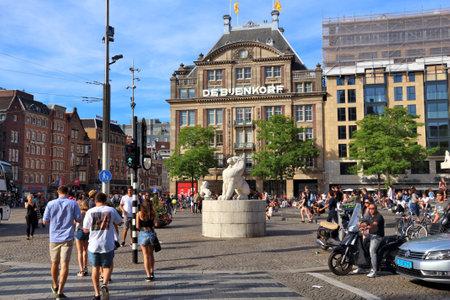 AMSTERDAM, NETHERLANDS - JULY 9, 2017: People visit Dam Square in Amsterdam, Netherlands. Amsterdam is the capital city of The Netherlands.