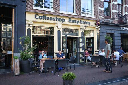 AMSTERDAM, NETHERLANDS - JULY 8, 2017: Coffee shop Easy Times in Amsterdam, Netherlands. Coffeeshops legally sell marijuana for personal consumption. Stockfoto - 128620700