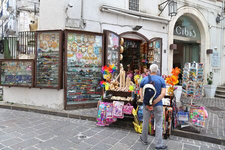 MONTE SANT ANGELO, ITALY - JUNE 6, 2017: People buy souvenirs in Monte Sant Angelo, Italy. The sanctuary town is part of UNESCO World Heritage Site: Longobards Places of Power.