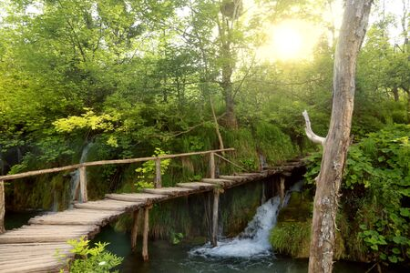 Plitvice Lakes National Park. Croatia waterfalls landscape. Tourist trail boardwalk and direct sunlight. Stock Photo