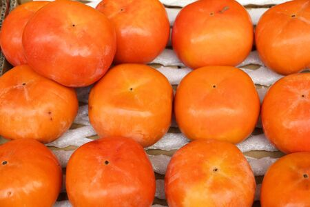 Japan persimmon fruit at a market in Tokyo. Persimmon (kaki) fruit are especially celebrated in autumn. Banque d'images