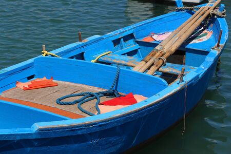 Blue fishing boat in Mediterranean harbor of Bari, Italy. Фото со стока