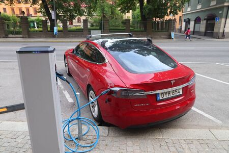 STOCKHOLM, SWEDEN - AUGUST 24, 2018: Tesla Model S electric car charging in Stockholm, Sweden. There are 520 registered vehicles per 1000 people in Sweden. Editorial