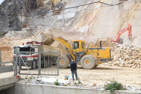 CARRARA, ITALY - APRIL 28, 2015: Heavy machines work in Fantiscritti valley marble stone quarry near Carrara, Italy. Carrara marble has been in use since Ancient Rome.