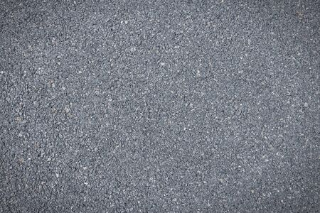 Asphalt concrete roadway pavement surface. Grey background.