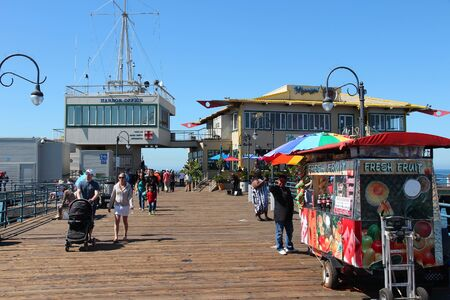 SANTA MONICA, UNITED STATES - APRIL 6, 2014: People visit the pier in Santa Monica, California. As of 2012 more than 7 million visitors from outside of LA county visited Santa Monica annually.