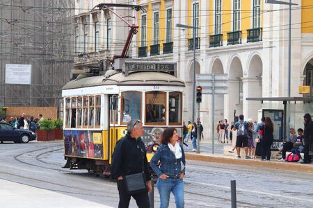 LISBON, PORTUGAL - JUNE 4, 2018: People ride the yellow tram in Praca Comercio square in Lisbon, Portugal. Lisbon's tram network dates back to 1873 and is famous for its old style small streetcars.