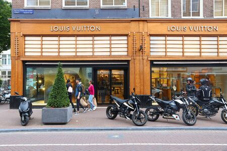 AMSTERDAM, NETHERLANDS - JULY 10, 2017: People visit Louis Vuitton shop at P.C. Hooftstraat in Amsterdam. Pieter Cornelis Hooftstraat is the ultimate upscale shopping street in the Netherlands.