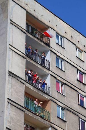 KATOWICE, POLAND - AUGUST 15, 2019: People visit the parade for Armed Forces Day in Katowice, Poland. Balconies overlooking the military parade.