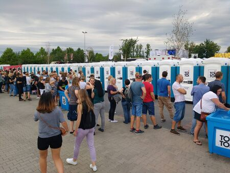 KATOWICE, POLAND - AUGUST 10, 2019: People visit massive portable restroom array at a music event Meskie Granie in Katowice, Poland.