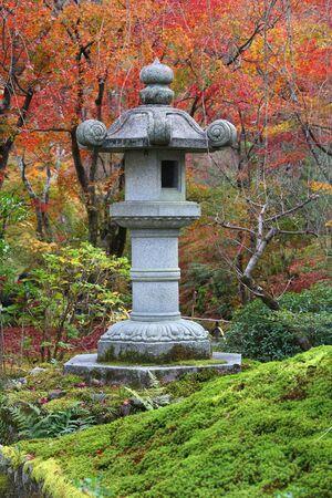 Japanese stone lantern inTenryuji gardens in Arashiyama, Kyoto. Autumn leaves.