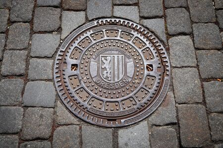 DRESDEN, GERMANY - MAY 10, 2018: Cast iron manhole cover (Kanaldeckel) for sewers of Dresden, the 12th biggest city in Germany.