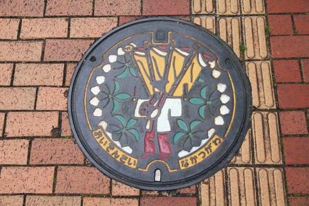 NAKATSUGAWA, JAPAN - MAY 2, 2012: Decorative sewer manhole cover of Nakatsugawa, a medium sized city in Gifu Prefecture of Japan.