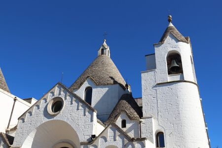 Alberobello, Italy - church in style of trulli traditional houses. Фото со стока