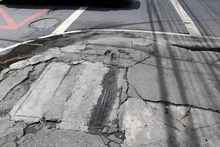 Dangerous city sidewalk in Manila, Philippines. Hazardous holes and damaged concrete.