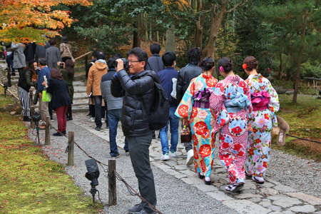 KYOTO, JAPAN - NOVEMBER 26, 2016: Women visit Kodaiji temple gardens in kimono costumes in Kyoto, Japan. 19.7 million foreign tourists visited Japan in 2015.