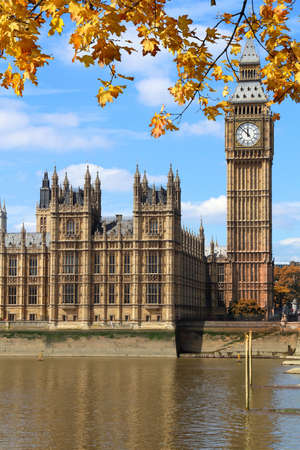 Big Ben and Houses of Parliament in London, UK. Autumn leaves.