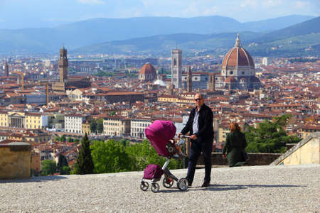 FLORENCE, ITALY - APRIL 30, 2015: A man walks with a baby stroller in Florence, Italy, a UNESCO World Heritage Site.
