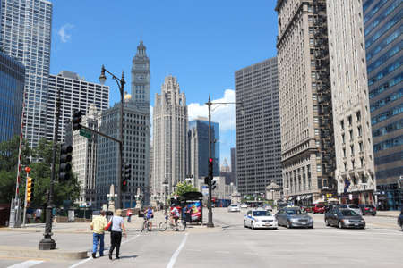 CHICAGO, USA - JUNE 27, 2013: People drive below Wrigley Building in Chicago. The building was completed in 1924 and is 130m tall. It is clad in glazed terra-cotta.