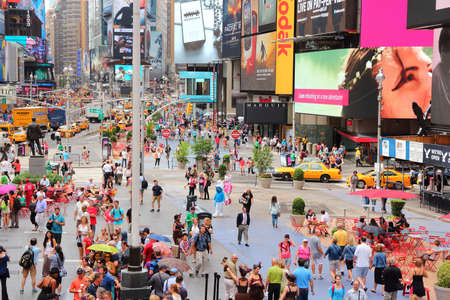 NEW YORK, USA - JULY 3, 2013: People visit Times Square in New York. The square at junction of Broadway and 7th Avenue has some 39 million visitors anually.
