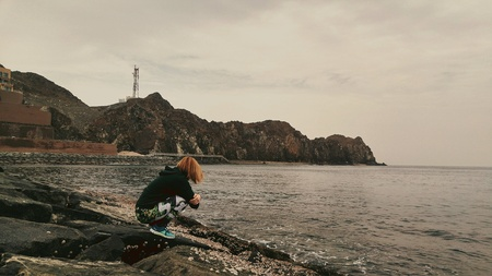 Young lady sitting on the rocks next to ocean alone, looking away, waiting