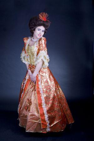 Tímida mujer vestida de rojo y vestido siglo 18.  Foto de archivo