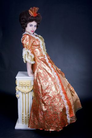 Beautiful 18th century coquette lady wearing vintage fashion leaning on a baroque column.