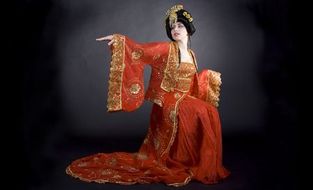 indian style sitting: Princess waiting for her prince to arrive. Elegant asian princess from a fairy tale dressed in golden and red.  Stock Photo