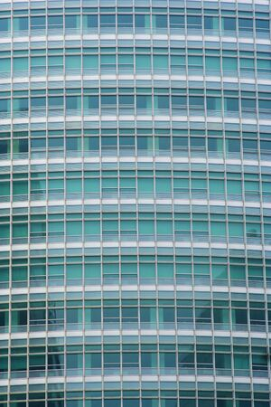 highriser: Full frame of a modern office building with transparent greenish windows. Stock Photo