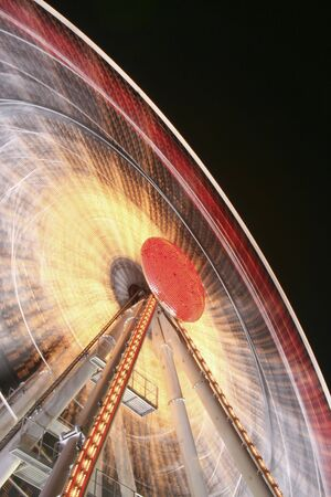 Close-up of a ferris wheel in the night leaving red and white trails. Stock Photo - 4243637