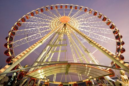 Wide angle view at a carnival ferris wheel in the dusk.