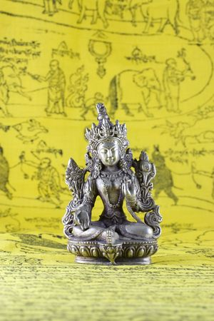tantric: The statuette of a dharmapala diety on a yellow background. Representation of tantric buddhism from Tibet.