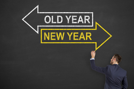 person writing: Business Person Writing on Blackboard Old Year or New Year