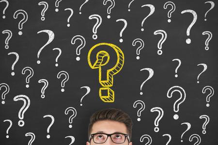 Man thinking on blackboard background Фото со стока